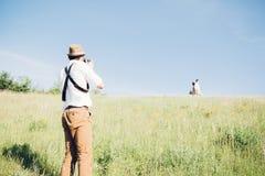 Ο γαμήλιος φωτογράφος παίρνει τις εικόνες της νύφης και του νεόνυμφου στη φύση, φωτογραφία Καλών Τεχνών στοκ φωτογραφίες