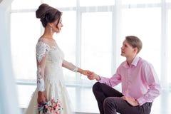 Ο γαμπρός κάθεται τη νύφη στέκεται Στοκ Εικόνες