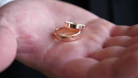 Ο γαμπρός κρατά στο κιβώτιο χεριών χρυσών γαμήλιων δαχτυλιδιών του, κινηματογράφηση σε πρώτο πλάνο φιλμ μικρού μήκους