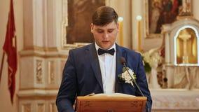 Ο γαμπρός στην εκκλησία διαβάζει το Ευαγγέλιο στο γάμο της Λέξη Θεών ` s απόθεμα βίντεο