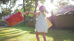 Ο γελώντας αγοραστής μικρών κοριτσιών απολαμβάνει τις νέες αγορές στις τσάντες εγγράφου και είναι περιστρέφεται με την ευτυχία στ φιλμ μικρού μήκους