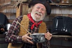 Ο γελώντας παλαιός μάγειρας κάουμποϋ κρατά μια κατσαρόλλα Στοκ Φωτογραφίες