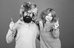 Ο γενειοφόροι πατέρας και το κορίτσι ατόμων φορούν τη ζωηρόχρωμη περούκα ενώ φάτε lollipop την καραμέλα Ο αγαπώντας πατέρας πράγμ στοκ εικόνα