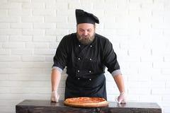 Ο γενειοφόρος αρχιμάγειρας αρχιμαγείρων προετοιμάζει τα γεύματα στοκ εικόνα με δικαίωμα ελεύθερης χρήσης