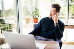 Ο γενειοφόρος επιχειρηματίας εργάζεται στο lap-top του στο γραφείο του και μιλά το τηλέφωνο και κοιτάζει μακριά Στοκ Εικόνες