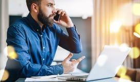 Ο γενειοφόρος επιχειρηματίας κάθεται στον πίνακα μπροστά από τον υπολογιστή, που μιλά στο τηλέφωνο κυττάρων Freelancer, σπίτι εργ Στοκ φωτογραφίες με δικαίωμα ελεύθερης χρήσης