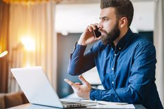 Ο γενειοφόρος επιχειρηματίας κάθεται στον πίνακα μπροστά από τον υπολογιστή, που μιλά στο τηλέφωνο κυττάρων Freelancer, σπίτι εργ Στοκ εικόνα με δικαίωμα ελεύθερης χρήσης