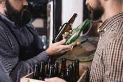 Ο γενειοφόρος ζυθοποιός παίρνει το μπουκάλι μπύρας γυαλιού χρώματος στο ζυθοποιείο Διαδικασία της κατασκευής μπύρας Στοκ Φωτογραφία