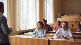 Ο γενειοφόρος καθηγητής ατόμων διαβάζει τη διάλεξη που μιλά και που ενώ οι σπουδαστές ακούνε και γράφουν τη συνεδρίαση απόθεμα βίντεο