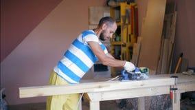 Ο γενειοφόρος μαυρισμένος βιοτέχνης απασχολείται στο ξύλο στο εργαστήριό του Τρομερός σε αργή κίνηση απόθεμα βίντεο