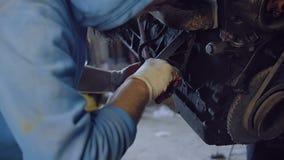 Ο γενειοφόρος μηχανικός σφίγγει το μπουλόνι με ένα εργαλείο στη φλούδα μιας αυτοκίνητης μηχανής που αναστέλλεται σε ένα κατάστημα φιλμ μικρού μήκους