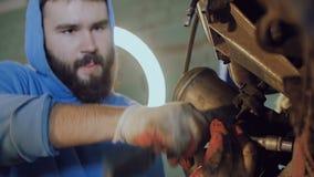 Ο γενειοφόρος μηχανικός σφίγγει το μπουλόνι με ένα εργαλείο στη φλούδα μιας αυτοκίνητης μηχανής που αναστέλλεται σε ένα κατάστημα απόθεμα βίντεο