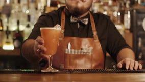 Ο γενειοφόρος μπάρμαν κινεί το γυαλί με το μικτό ποτό προς τη κάμερα με το χέρι απόθεμα βίντεο