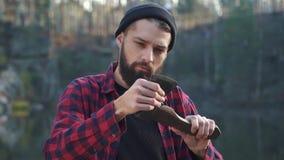 Ο γενειοφόρος νεαρός άνδρας εξετάζει το τσεκούρι του Βάναυσος σοβαρός τύπος με το τσεκούρι υπαίθρια απόθεμα βίντεο
