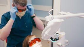 Ο γενειοφόρος οδοντίατρος προετοιμάζει τον ασθενή στα δόντια που λευκαίνουν στο οδοντικό γραφείο απόθεμα βίντεο