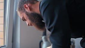 Ο γενειοφόρος ράφτης κάνει ένα σχέδιο στο ύφασμα πριν από ράβει τα μοντέρνα ενδύματα φιλμ μικρού μήκους