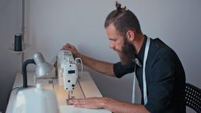 Ο γενειοφόρος ράφτης της Νίκαιας hipster ράβει τα μοντέρνα ενδύματα στο στούντιο σχεδίου φιλμ μικρού μήκους