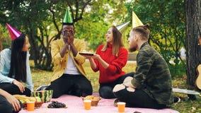 Ο γενειοφόρος τύπος αφροαμερικάνων έχει τη γιορτή γενεθλίων στο πάρκο με τα κεριά στο κέικ και γελά απολαμβάνοντας την έκπληξη στοκ φωτογραφία με δικαίωμα ελεύθερης χρήσης