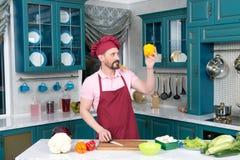 Ο γενειοφόρος τύπος στην κόκκινη ποδιά και το κόκκινο καπέλο εξετάζει την κίτρινη πάπρικα Στοκ Εικόνες