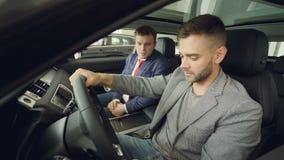 Ο γενειοφόρος τύπος συζητά τα χαρακτηριστικά γνωρίσματα αυτοκινήτων με πωλητών συνεδρίασης μαζί αυτοκίνητο και την ομιλία εσωτερι φιλμ μικρού μήκους