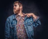 Ο γενειοφόρος τύπος hipster που ντύνεται στο σακάκι τζιν αισθάνεται ανήσυχος και τραβά πίσω το περιλαίμιο πουκάμισων σε ένα σκοτε στοκ εικόνες με δικαίωμα ελεύθερης χρήσης