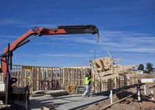 Ο γερανός ανυψώνει τα ζευκτόντα επάνω στα καινούργια σπίτια κάτω από την κατασκευή Στοκ Εικόνες