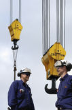ο γερανός γαντζώνει τους εργαζομένους περιοχών Στοκ εικόνα με δικαίωμα ελεύθερης χρήσης
