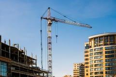 Ο γερανός κατασκευής μεταξύ του καινούργιου σπιτιού και του ατελούς σπιτιού Στοκ Φωτογραφία