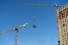 Ο γερανός μεγάλου υψομέτρου ανυψώνει το φορτίο, ενάντια στο μπλε ουρανό Στοκ εικόνες με δικαίωμα ελεύθερης χρήσης