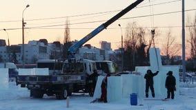 Ο γερανός ξεφορτώνει τα κομμάτια πάγου για την πόλη πάγου απόθεμα βίντεο