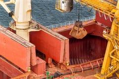 Ο γερανός ξεφορτώνει το σιδηρομετάλλευμα στο λιμάνι Εμπόριο στις πρώτες ύλες Εργασία σε έναν λιμένα στη θάλασσα της Βαλτικής Στοκ Εικόνες