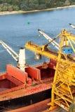 Ο γερανός ξεφορτώνει το σιδηρομετάλλευμα στο λιμάνι Εμπόριο στις πρώτες ύλες Εργασία σε έναν λιμένα στη θάλασσα της Βαλτικής Στοκ Εικόνα