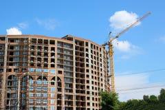 Ο γερανός οικοδόμησης και το κτήριο ενάντια στο μπλε ουρανό Στοκ φωτογραφίες με δικαίωμα ελεύθερης χρήσης