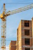Ο γερανός χτίζει το multi-storey κατοικημένο σπίτι Στοκ Εικόνες