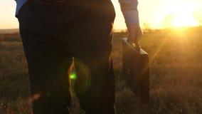 Ο γεωπόνος πηγαίνει στον τομέα την άνοιξη με τα έγγραφα στις ακτίνες του ηλιοβασιλέματος επιχειρηματίας με έναν χαρτοφύλακα στο χ απόθεμα βίντεο