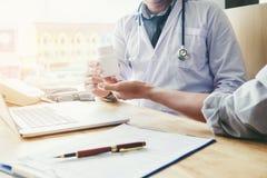 Ο γιατρός ή ο παθολόγος συστήνει την ιατρική συνταγή χαπιών στο αρσενικό Στοκ Εικόνες