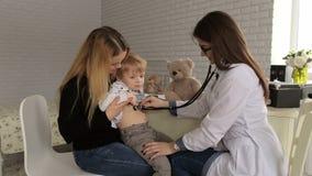 Ο γιατρός ακούει τους πνεύμονες με ένα στηθοσκόπιο ένα μικρό αγόρι σε ένα νοσοκομείο απόθεμα βίντεο