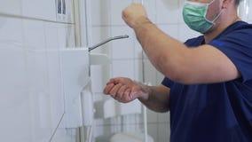 Ο γιατρός απολυμαίνει και πλύση τα χέρια του ξηρά πρίν εισάγει το λειτουργούν δωμάτιο Χειρουργική απολύμανση χεριών emergency φιλμ μικρού μήκους