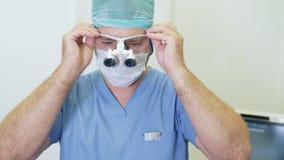 Ο γιατρός βάζει στην ενίσχυση των διοφθαλμικών γυαλιών και τους ρυθμίζει, που προετοιμάζονται για τη χειρουργική επέμβαση στην κλ απόθεμα βίντεο