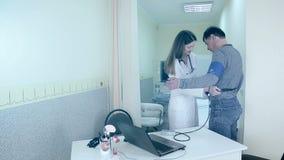 Ο γιατρός γυναικών βοηθά να φορέσει μια διαγνωστική συσκευή καρδιών για τον ασθενή απόθεμα βίντεο