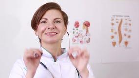 Ο γιατρός γυναικών με ένα στηθοσκόπιο βγάζει τα γυαλιά του camera smiling απόθεμα βίντεο