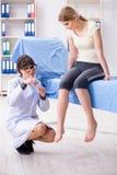 Ο γιατρός γυναικών που ελέγχει με το αισθητήριο σφυρί στοκ φωτογραφίες