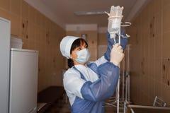Ο γιατρός γυναικών στα ιατρικά γάντια σε μια προστατευτική μάσκα στέκεται και κρατά μια σταλαγματιά στα χέρια που είναι σε έναν θ στοκ φωτογραφίες