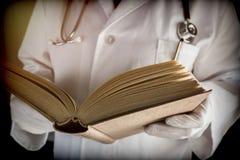 Ο γιατρός διαβάζει το ιατρικό βιβλίο σε ένα νοσοκομείο στοκ εικόνες