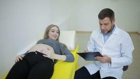 Ο γιατρός εξετάζει μια έγκυο γυναίκα και γράφει τα αποτελέσματα στην ιατρική κάρτα απόθεμα βίντεο