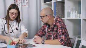 Ο γιατρός εξετάζει μια ακτίνα X του βραχίονα του ασθενή Ένας ασθενής με μια επιδεμένη συνεδρίαση καρπών στο γραφείο του γιατρού απόθεμα βίντεο