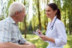 Ο γιατρός εξετάζει τον ηληκιωμένο στο θερινό πάρκο στοκ εικόνα