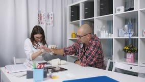 Ο γιατρός εξετάζει τον τραυματισμένο καρπό ενός υπομονετικού ατόμου φιλμ μικρού μήκους