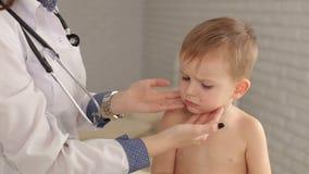 Ο γιατρός εξετάζει το λαιμό ενός άρρωστου παιδιού στο νοσοκομείο φιλμ μικρού μήκους