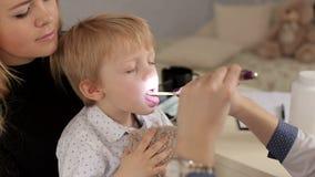 Ο γιατρός εξετάζει το λαιμό και το στόμα σε ένα μικρό παιδί απόθεμα βίντεο